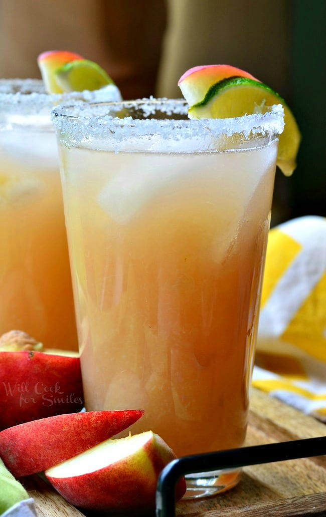 Peach Margarita is presented in a tall glass. The liquid is beige in color. There is floating ice in the glass. The rim of the glass is covered in coarse salt. A lime and fresh peach slice also sit on the rim of the glass. On the wooden board below the glass, sit fresh peach slices.