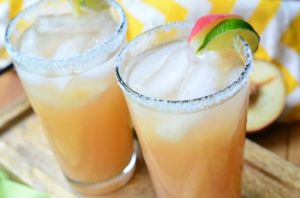 Top view of two Peach Margaritas. Each Peach Margarita is presented in a tall glass. The liquid is beige in color. There is floating ice in the glasses. The rim of the glasses are covered in coarse salt. A lime and fresh peach slice also sit on the rims of the glasses.
