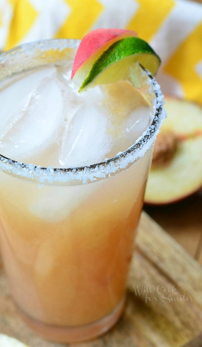 Peach Margarita is presented in a tall glass. The liquid is beige in color. There is floating ice in the glass. The rim of the glass is covered in coarse salt. A lime and fresh peach slice also sit on the rim of the glass.