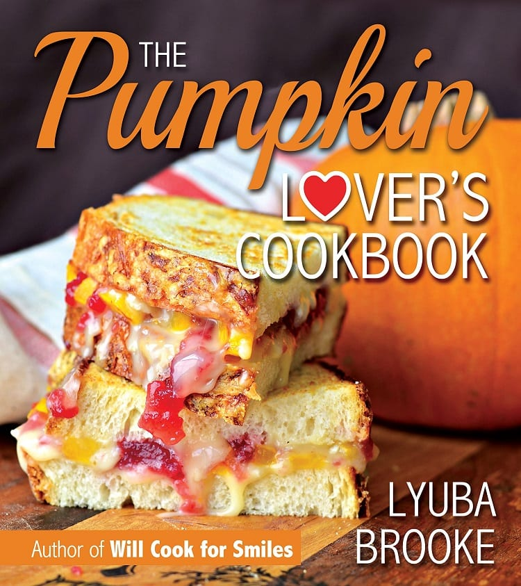the pumpkin lovers cookbook cover with a sandwich cut in half with cheese, pumpkin, and cranberry inside and a pumpkin in the background