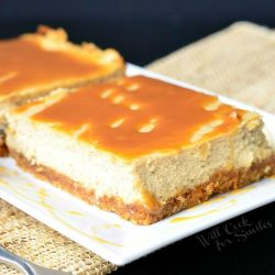 2 portions of caramel macchiato cheesecake bars on a white rectangular plate with a fork n the foreground