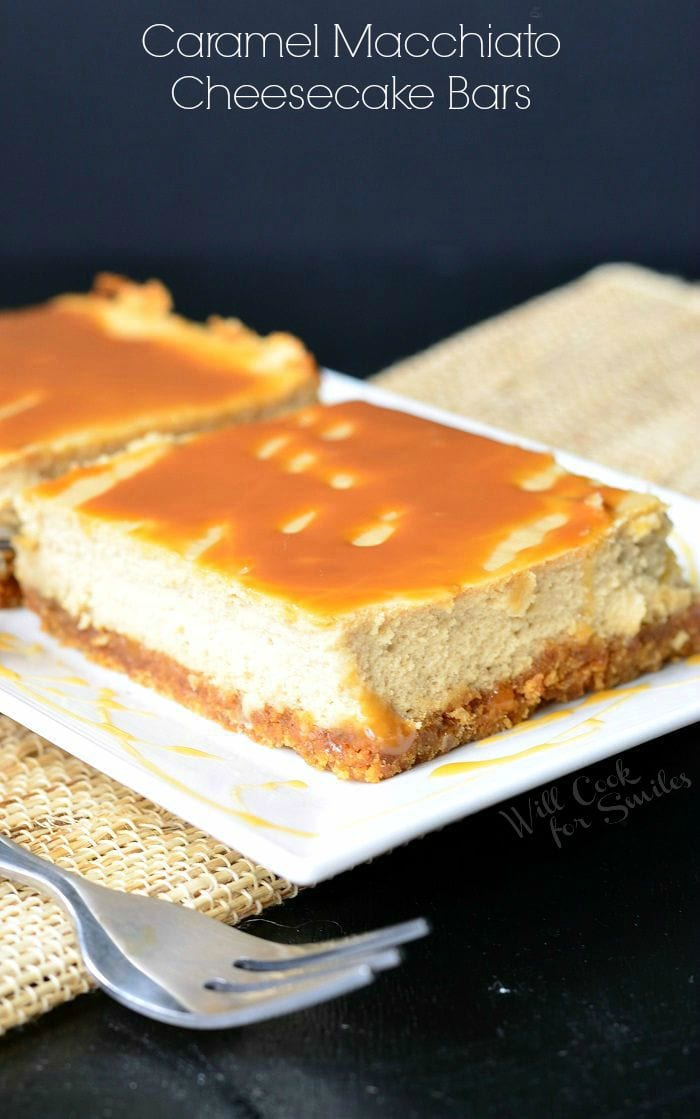 Caramel Macchiato Cheesecake Bars are on a white plate. Caramel is drizzled on top of the bars, as well as on the plate. A fork is laid to the left side of the plate.