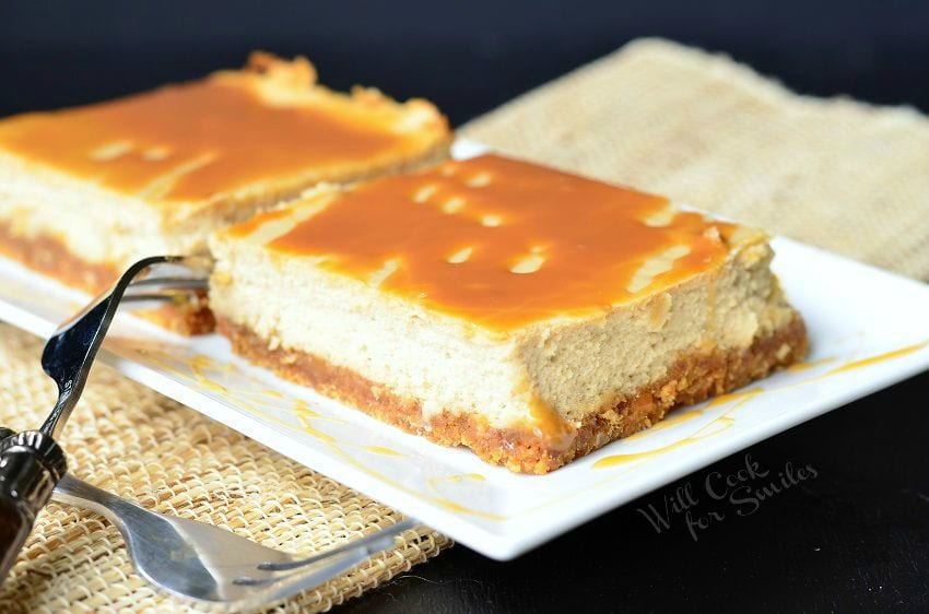 Caramel Macchiato Cheesecake Bars are on a white plate. Caramel is drizzled on top of the bars, as well as on the plate. Forks are criss-crossed to the left side of the plate.