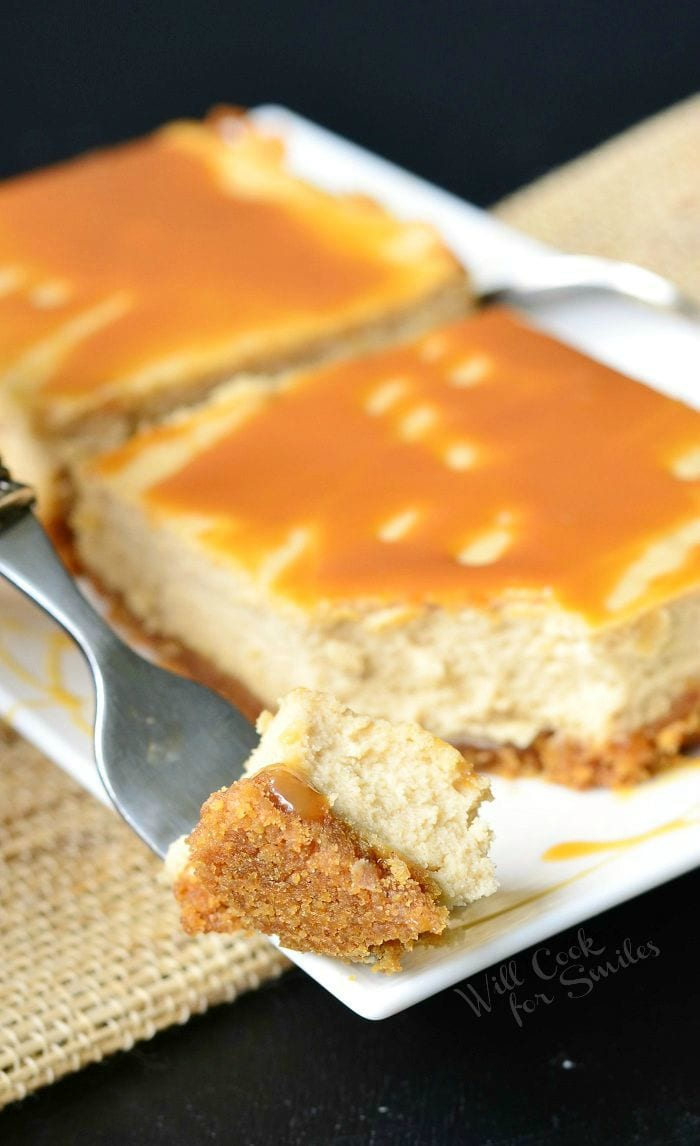 Caramel Macchiato Cheesecake Bars are on a white plate. Caramel is drizzled on top of the bars, as well as on the plate. A fork holds a bite of one of the bars.