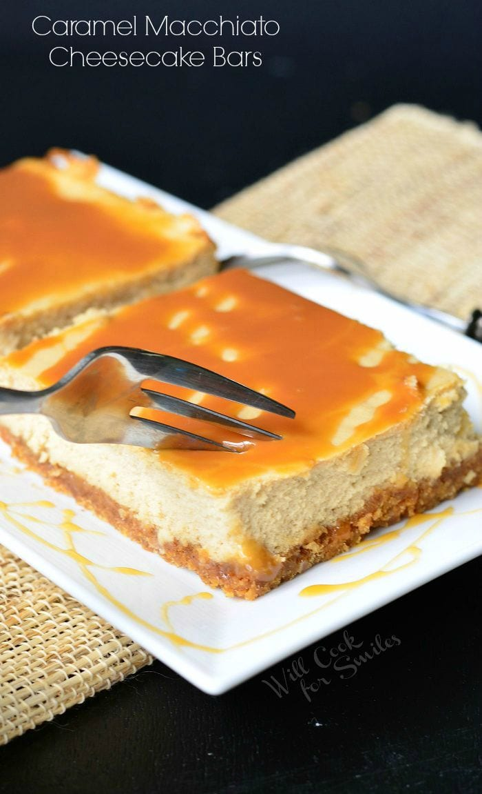 Caramel Macchiato Cheesecake Bars are on a white plate. Caramel is drizzled on top of the bars, as well as on the plate. A fork is inserted into one of the bars.