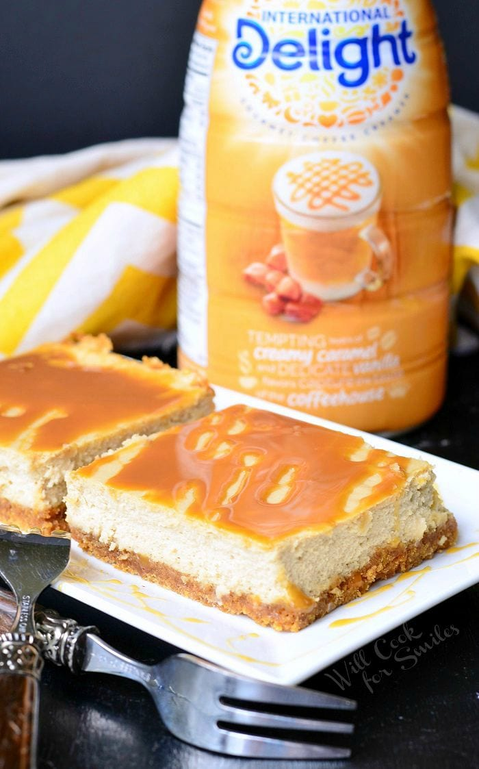 Caramel Macchiato Cheesecake Bars are on a white plate with the forks set to the side. Caramel is drizzled on top of the bars, as well as on the plate. Caramel coffee creamer is sitting on the table in the background.