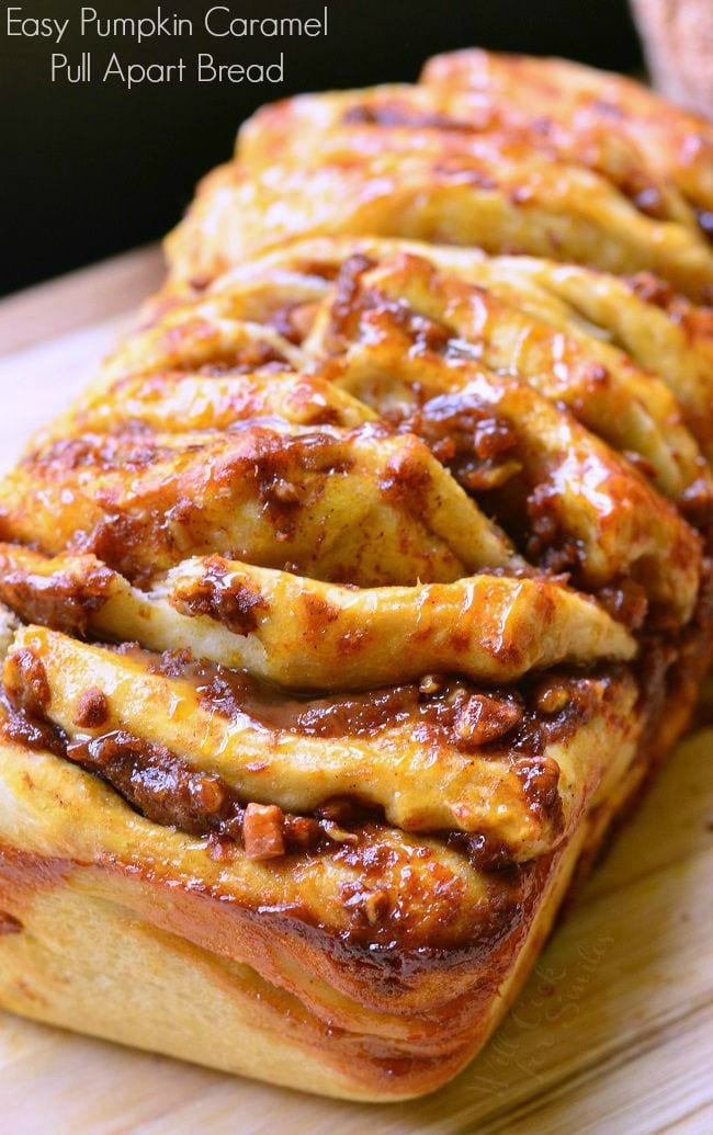 Easy Caramel Pumpkin Pull Apart Bread sits on a cutting board. Each layer is slathered in pumpkin, caramel, and pecans. There is a caramel sauce drizzled on top as well.
