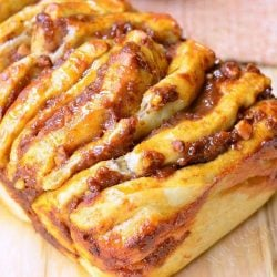 close up view of easy pumpkin caramel pull apart bread on a wooden table with a brown cloth in the background