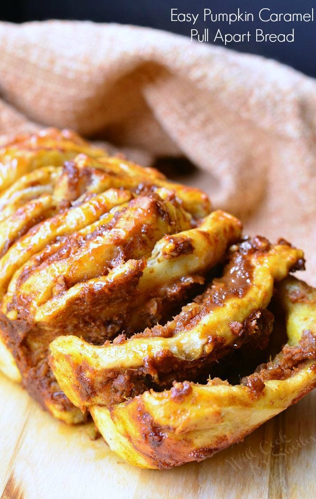 Easy Caramel Pumpkin Pull Apart Bread sits on a cutting board. The first two layers slightly pulled. Each layer is slathered in pumpkin, caramel, and pecans. There is a caramel sauce drizzled on top as well.