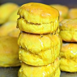 stacks of honey pumpkin biscuits on a metal sheet tray on a wooden table as viewed close up