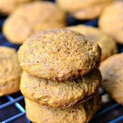 3 pumpkin pudding cookies stacked on a wire cooling rack with more cookies in the background