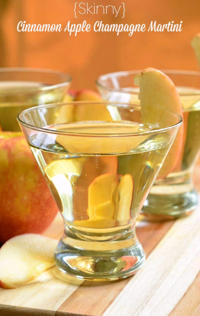 {Skinny} Cinnamon Apple Champagne Martinis in short martini glasses with a sliced apple placed on the rim of the glass.