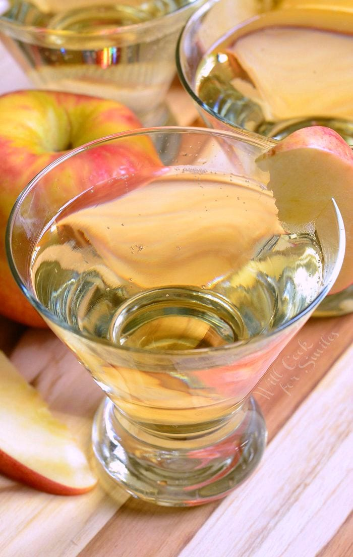 Top view of {Skinny} Cinnamon Apple Champagne Martinis in short martini glasses with a sliced apple placed on the rim of each glass. On the table there are also apples and apple slices.
