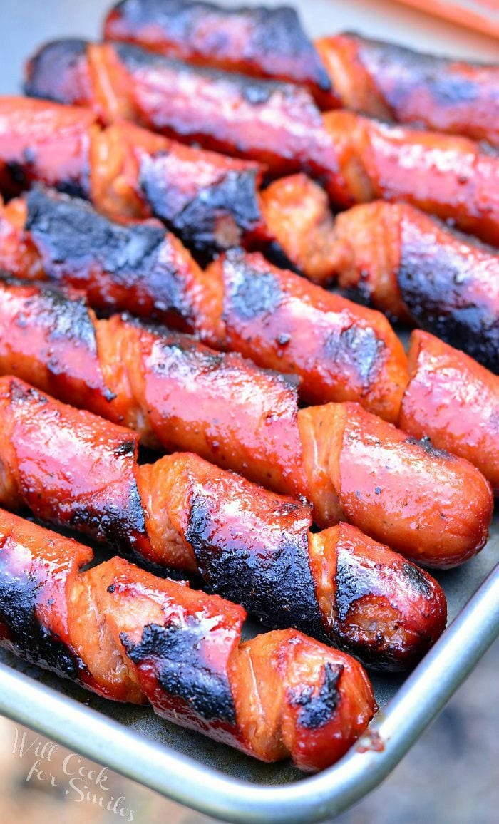 Spiral cut Hot Dogs lay side by side in a pan. They appear juicy and have black grill marks on them.