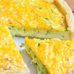 close up view of 1 slice seperated from sriracha zucchini and cheese quiche on a wood table as shown from above