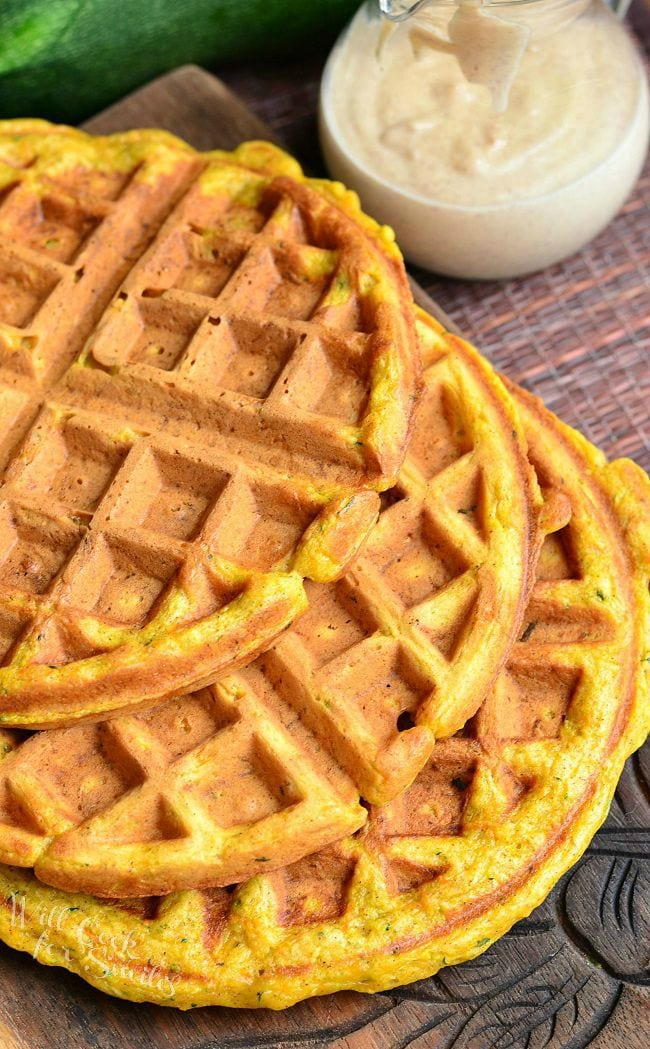 Top view of three Zucchini Carrot Cake Waffles which are laid on a wooden board. The waffles are overlapping each other. Off to the back, right side is a glass container. This container has cinnamon cream cheese sauce in it.