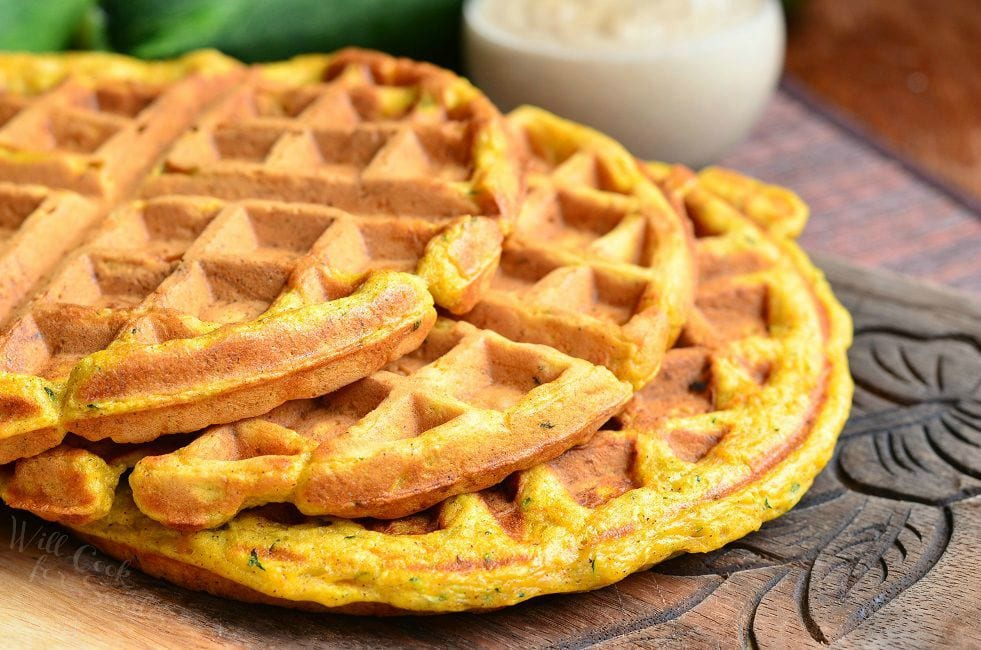 Three Zucchini Carrot Cake Waffles are laid on a wooden board. They are laid in a way that they are overlapping each other.