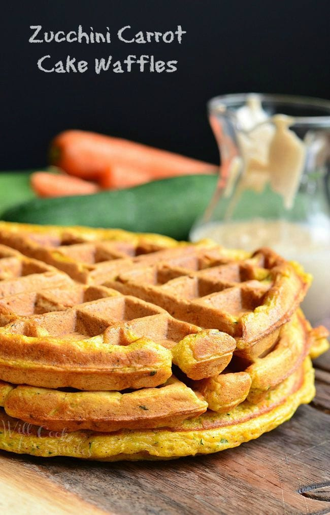Side view of three Zucchini Carrot Cake Waffles all stacked on top of each other. In the background is a glass container which holds the cinnamon cream cheese sauce.