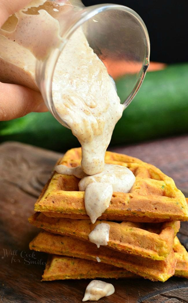 Four pieces of Zucchini Carrot Cake Waffles are stacked up. A glass container is being tilted over the waffles. A cinnamon cream cheese sauce is coming out of the container onto the top of the waffles and dripping down the side.