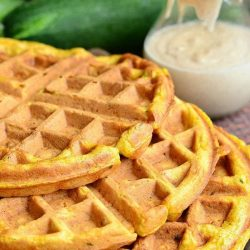 3 zucchini carrot cake waffles stacked on a wooden cutting board