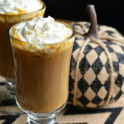 Dessert coffee glass mug filled with pumpkin white chocolate mocha latte on a white and black zig zag placemat with an additional glass in the background to the left next to a fabric pumpkin decoration