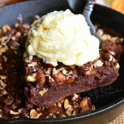 1 slice of brownie being held above black skillet filled with a small batch of pumpkin turtle brownie on a wooden table as viewed close up