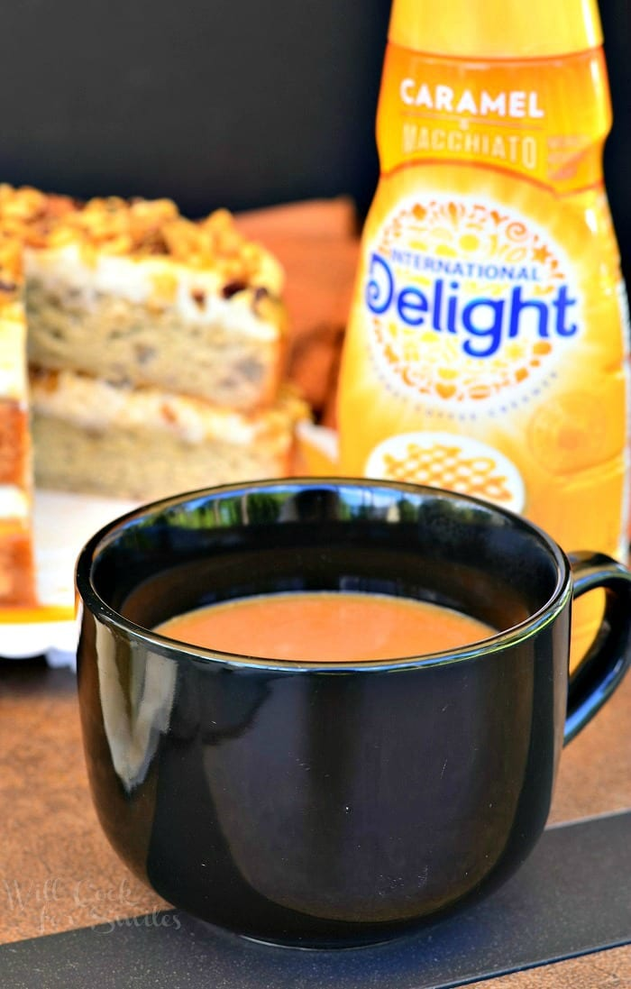 coffee in a black cup with Caramel delight creamer and Banana Nut Cake in the background