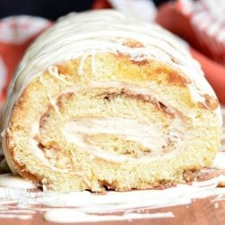 View from the front of cinnamon roll cake roll on a wooden board with icing drizzled across the top of the roll and a white and red cloth in the background