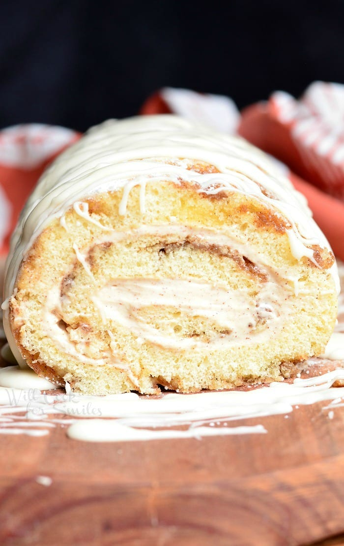 Cinnamon Roll Cake Roll with icing all over the top on a cutting board