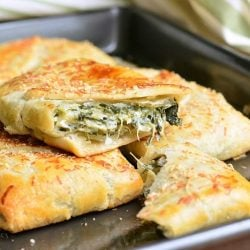 3 spinach artichoke hand pies on a metal baking pan with the top pie broken in half to show contents as viewed close up
