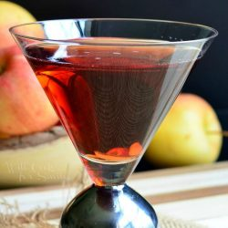Side view of a decorative martini glass with washington apple martini on a brown placemat with a bowl of apples in the background to the left