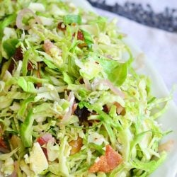 small white bowl filled with a bacon and blue brussels sprouts salad with warm bacon vinaigrette on a white table cloth covered table