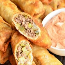 stacked cheeseburger eggrolls on a wooden tray with a small white bowl filled with dipping sauce and an eggroll cut in half and sitting on top of the stack of eggrolls