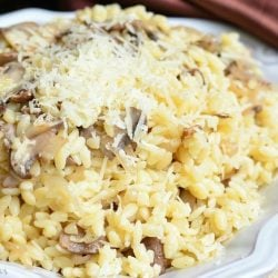 decorative plate topped with parmesan mushroom orzo on a burlap placemat with a redish brown cloth in the background as viewed close up