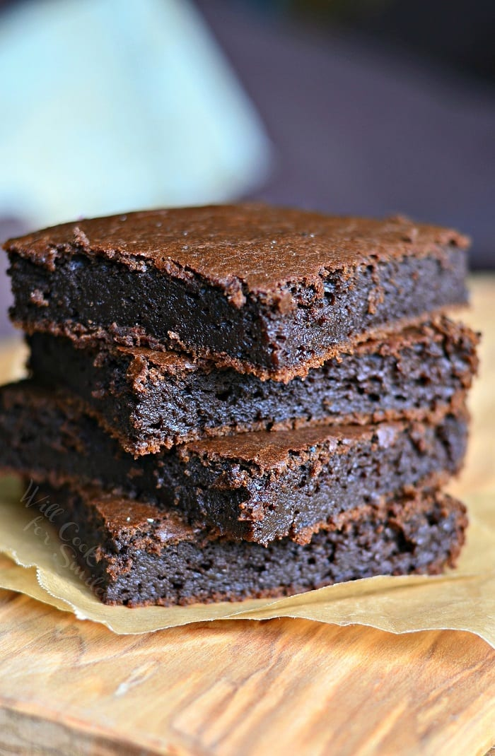 Pumpkin Brownies stacked on top of each other on a parchment paper