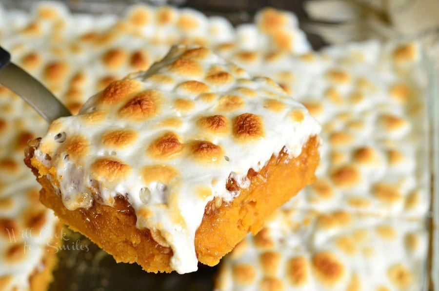 sweet potato casserole with marshmallow topping being lifted out of glass baking pan with a spatula