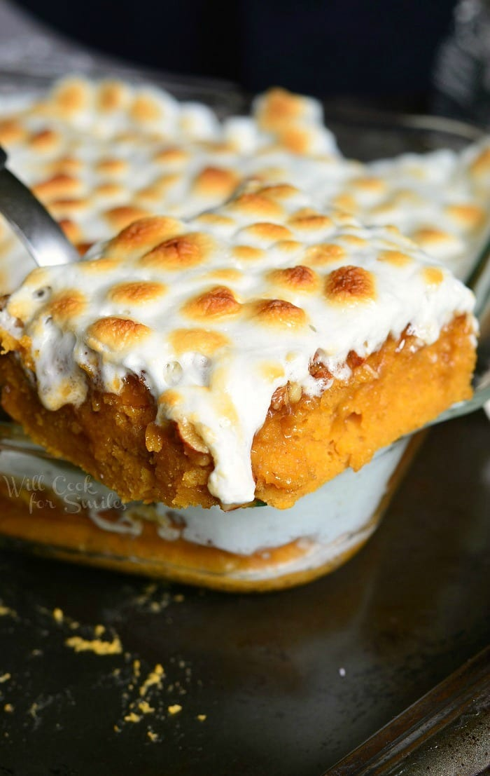 Sweet Potato Casserole Cake with melted marshmallows on top being lifted out by a spatula