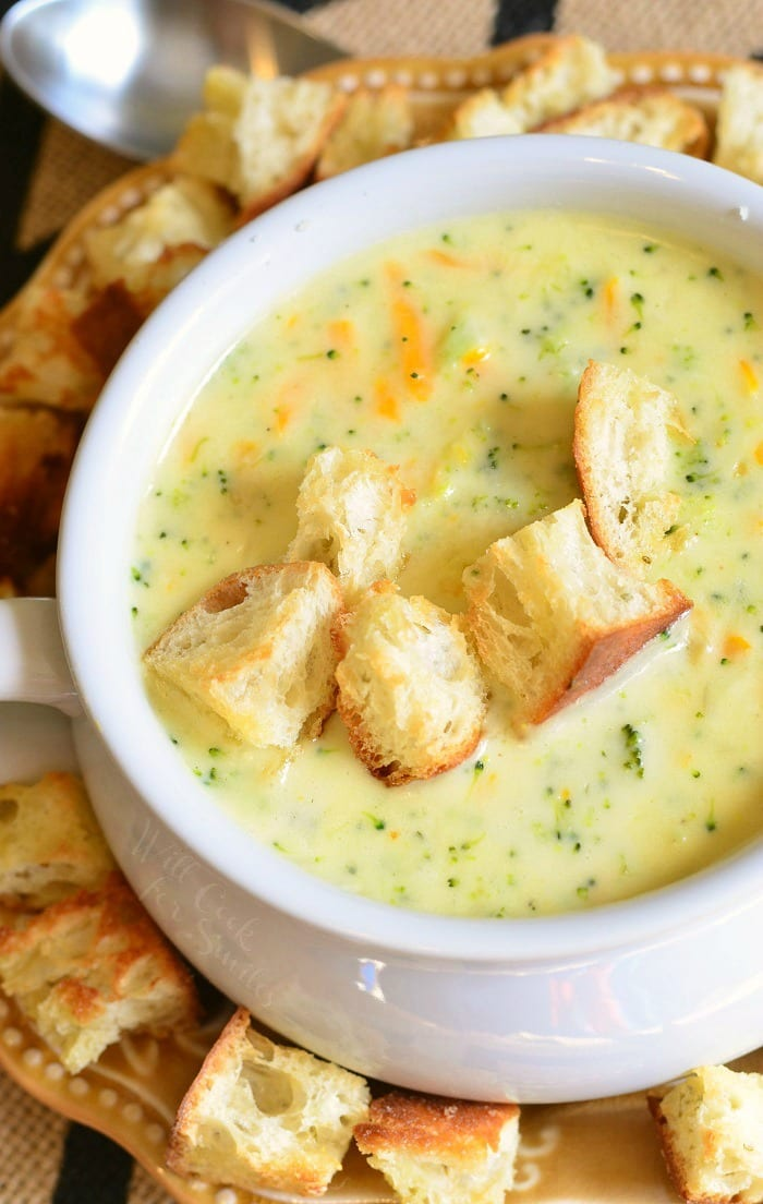 top view Asiago Broccoli Cheese Soup in a white soup bowl with cut up pieces of crusty bread on top and around the bottom of the bowl
