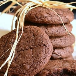 2 chocolate chocolate chip gingersnap cookies in front of additional cookies stacked behind on a white cloth while all sit on a wooden table