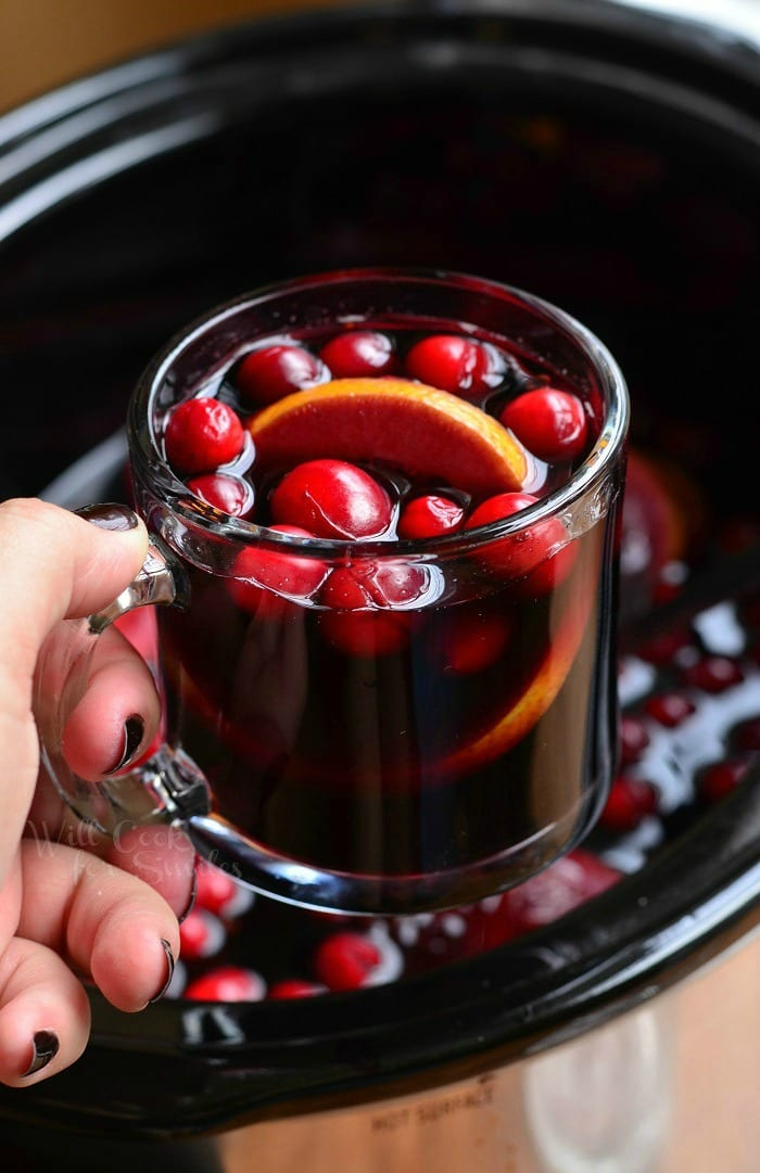 holding Orange Cranberry Sangria in a glass mug with orange and cranberries inside