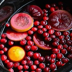 a crock pot shown cooking spiced orange cranberry sangria