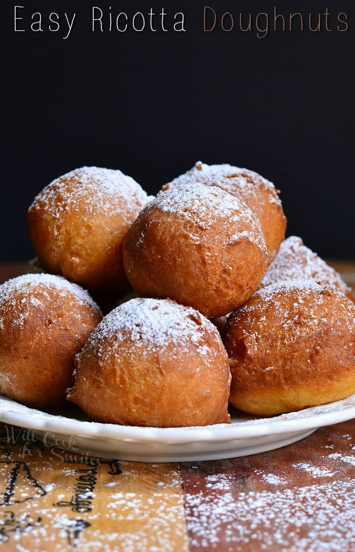 Doughnut holes with powdered sugar on top stacked on a white plate