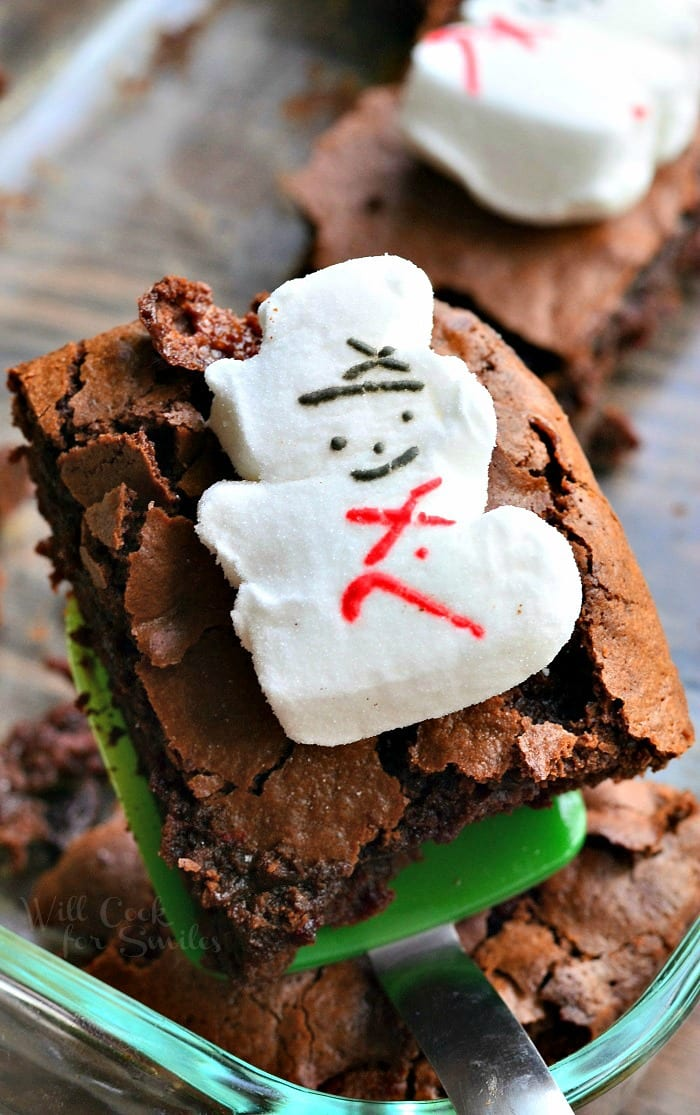 Brownies with snowman marshmallows on top on a green spatula