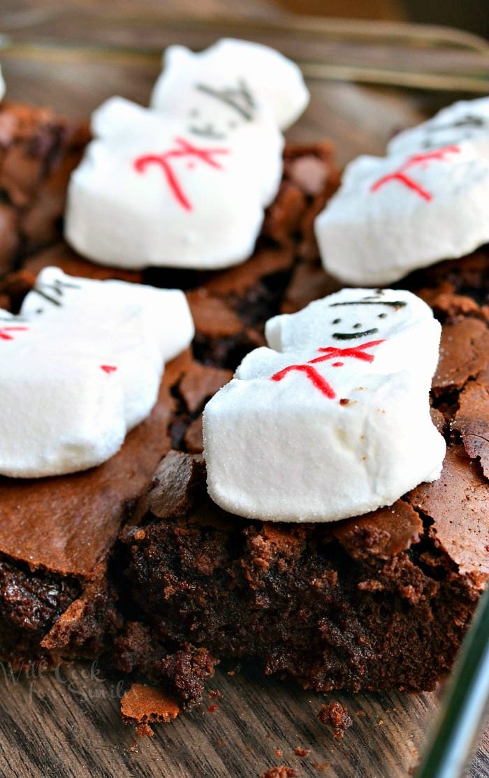 Brownies with snowman marshmallows on top in a clear glass baking pan