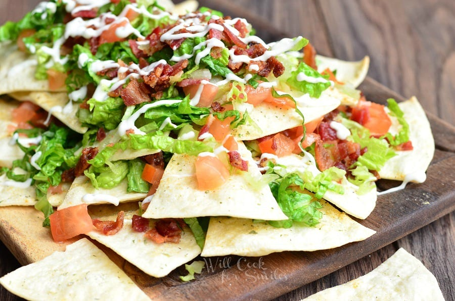BLT Nachos with lettuce, tomato, and bacon on a wood cutting board
