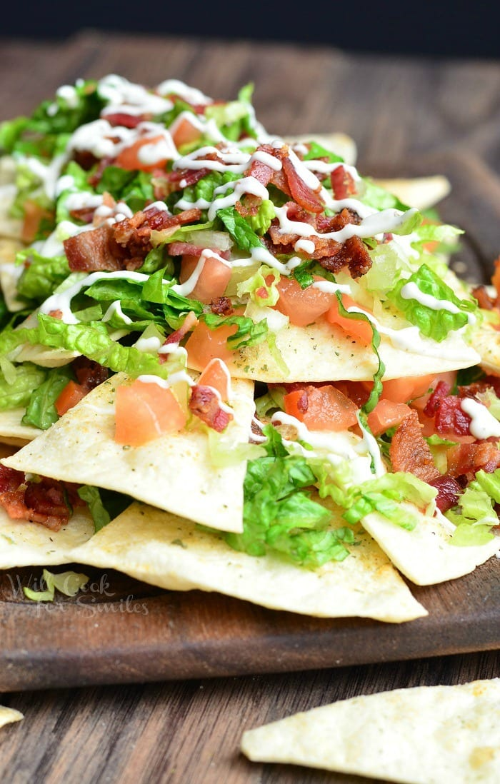 BLT Nachos with lettuce, tomato, and bacon, on a wood cutting board