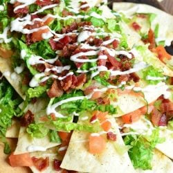 View from above of a wooden platter with BLT nachos and homemade baked cool ranch tortilla chips on a wooden table