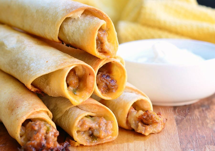 Jalapeño Sausage and Cheese Taquitos stacked on a cutting board