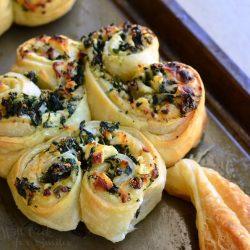 spinach and feta pastry shamrocks on a baking sheet pan as viewed close up