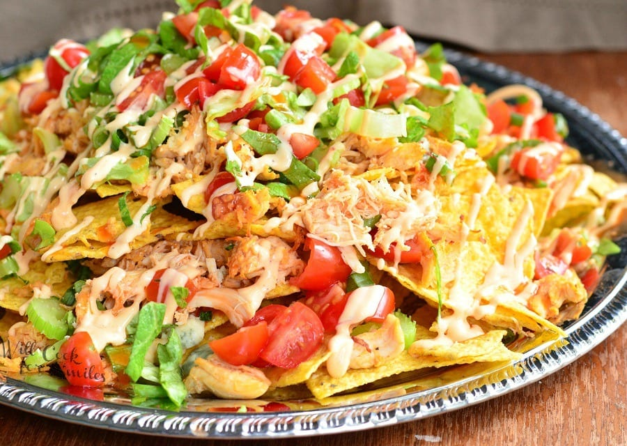 Buffalo Chicken Nachos made with crispy tortilla chips, spicy buffalo sauce coated shredded chicken, blue cheese, veggies, more cheese and buffalo ranch dressing. #nachos #chicken #spicy #buffalochicken #chickennachos